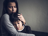 Sad little boy being hugged by his mother at home. Parenthood, Love and togetherness concept.