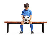 Sad little footballer seated on a wooden bench isolated on white background
