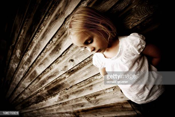 Sad Little Girl leaning on the side of a house