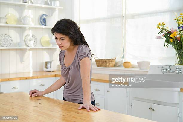 Sad looking woman standing in kitchen