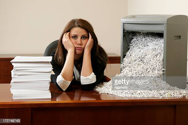 A sad looking women shredding office papers