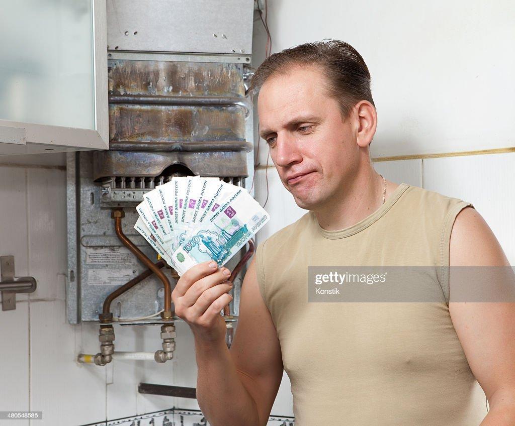 Homem triste conta dinheiro para reparação de um aquecedor de água a gás : Foto de stock