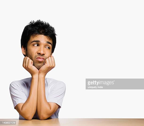 Sad man looking sideways with his hands on chin