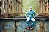 Sad man sitting on the abandoned rusty bridge. Concept for sadness, loneliness and more.