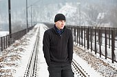 Young man on railroad track in winter