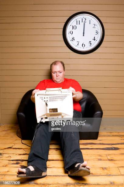 Sad Man Sitting on Couch and Watching Television in Lap