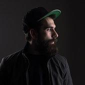 Sad man wearing baseball cap looking away. High contrast low key dark shadow portrait over black background.