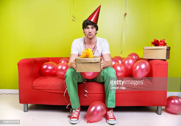 Sad Man Wearing Party Hat Holding Present with Balloons