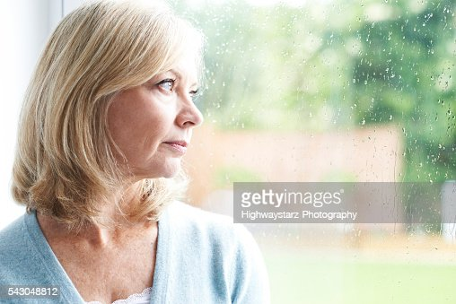 Sad Mature Woman Suffering From Agoraphobia Looking Out Of Windo : Stock Photo