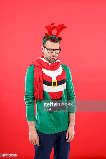 Sad nerd man in funny winter outfit against red background