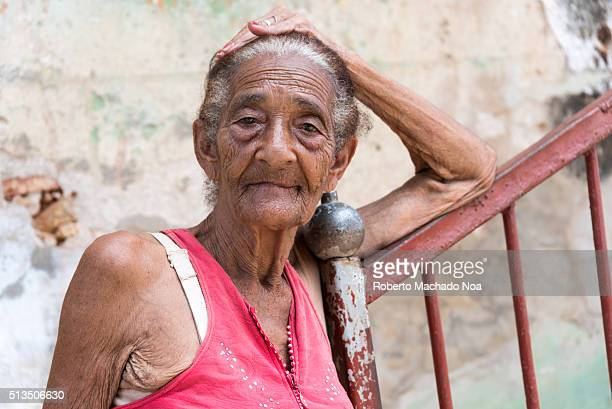 Sad old mixed race Cuban senior woman reclining on stairs handrail Relaxing on a refreshing tropical day