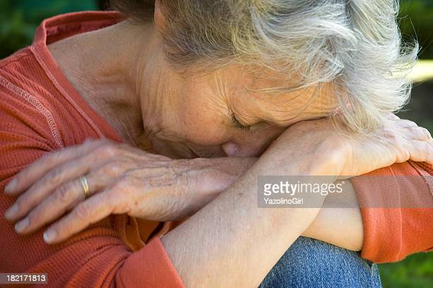 A sad old woman with her head in her arms