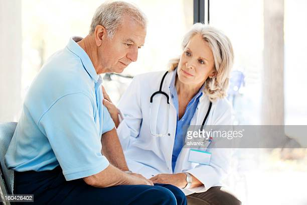 Sad patient being recomforted by a doctor