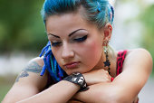 Sad but beautiful punk girl sitting outdoors