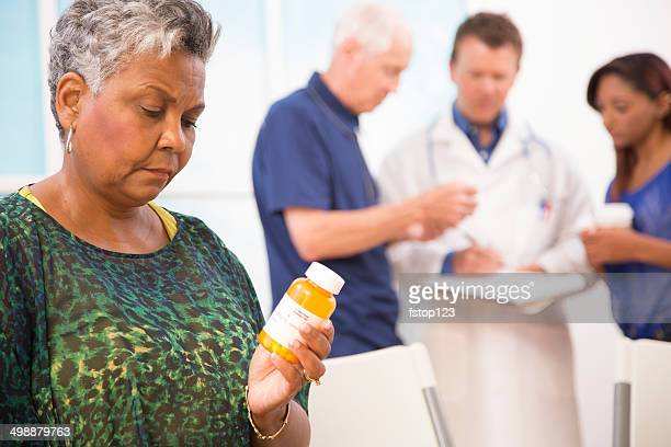 Sad senior woman abuses prescription medications. Doctor, patients background.