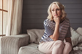 Beautiful sad senior woman is leaning on her hand and looking downward while sitting on couch at home