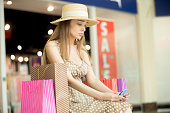 Sad young pretty woman sitting in shopping mall with shopping bag around thinking. She is holding credit cards looking upset as no money left. Buying too much on expensive shopping time concept