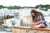 Sad teen complaining sitting on a ledge on vacation