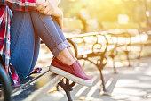 Sad teenage girl sitting on the park bench