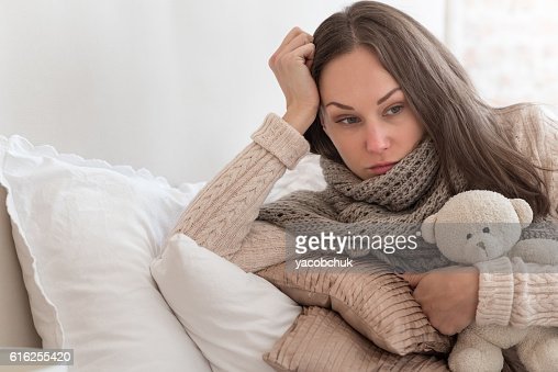 Sad thoughtful woman lying on pillows : Foto de stock
