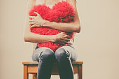 Broken heart love concept. Sad unhappy woman hugging red heart pillow