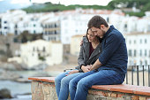 Sad woman and man comforting her on a ledge with a town in the background