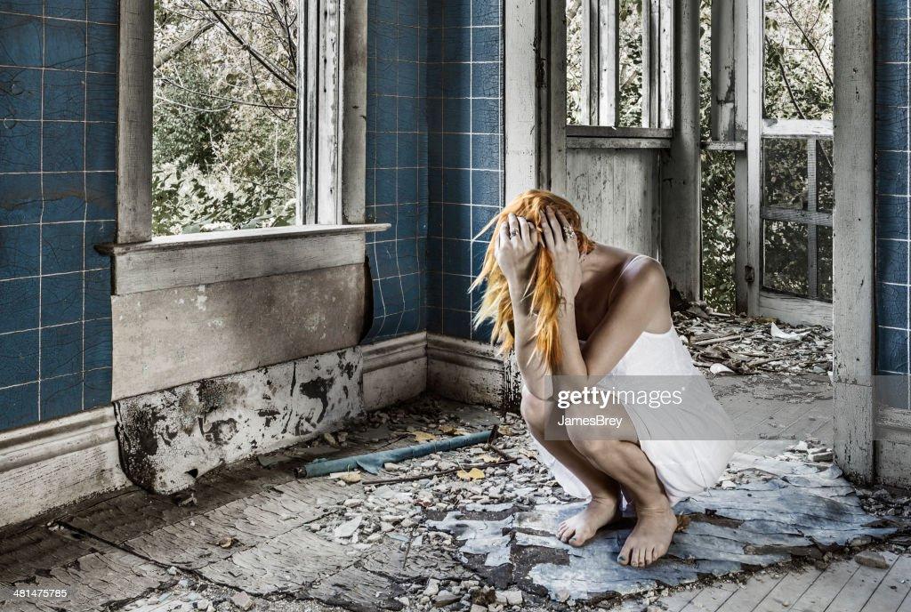 Sad Woman Crouching, Sobbing Amid Ruins