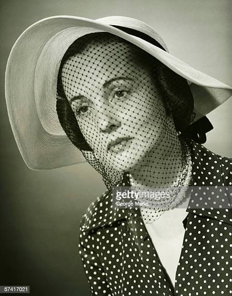 Sad woman in hat with veil posing in studio, (B&W), (Close-up), (Portrait)