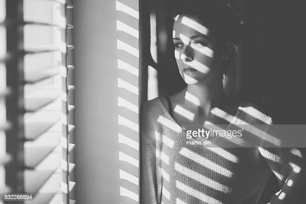 Sad woman looking through the window