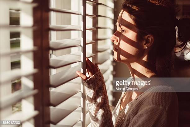 Sad woman looking through the window