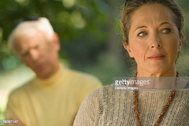 A sad woman, man blurred in the background.