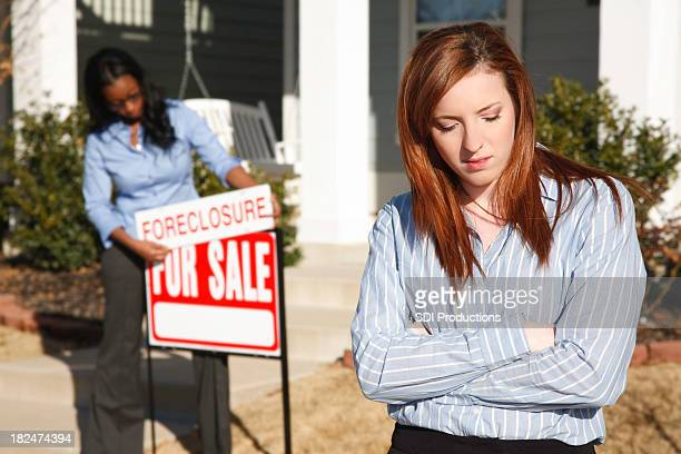 Sad Woman Outside Home While Realtor Puts up Foreclosure Sign