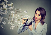 Sad woman showing her wallet with money dollar banknotes flying out away
