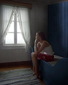 Sad Woman Sitting Alone in Room, daydreaming, side view