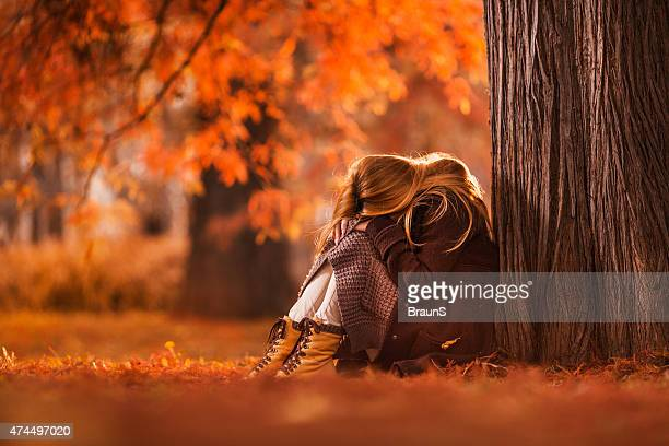 Sad woman sitting in the park during autumn day.