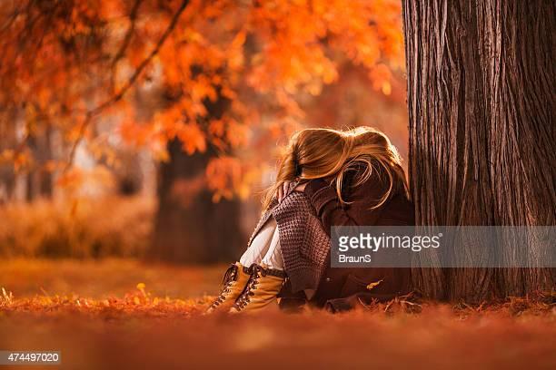 Triste donna seduta nel parco in autunno giorno.