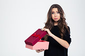 Portrait of a sad woman standing with opened gift box isolated on a white background and looking at camera