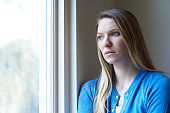 Sad Woman Suffering From Depression Looking Out Of Window