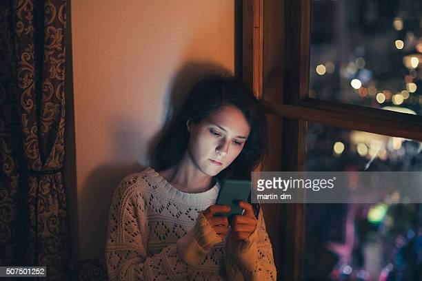 Sad woman texting at home