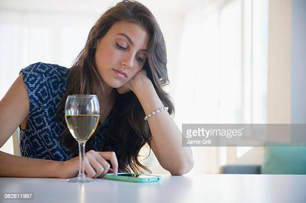 Sad woman with glass of wine texting