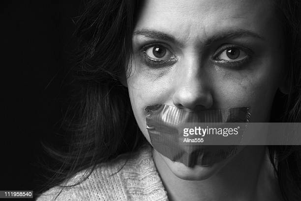 Sad woman's face with duct taped mouth and smeared makeup