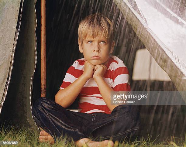 Sad Young Boy Camping in the Rain
