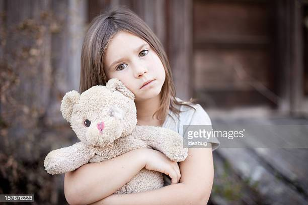 Sad Young Girl Hugging Old, Raggedy Teddy Bear