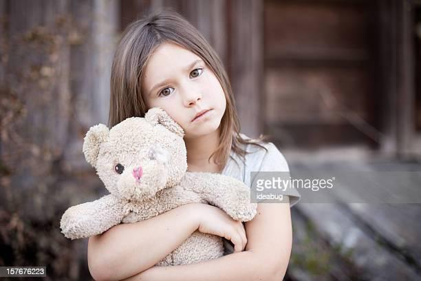 Traurige junge Mädchen umarmen Teddybär, Raggedy alten
