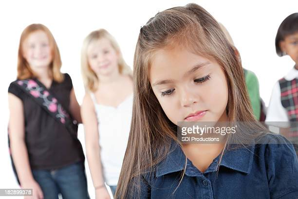 Triste jeune fille devant ses camarades de classe