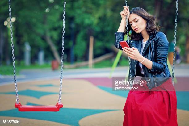 Sad young girl is sitting on the swind and looking her mobile phone