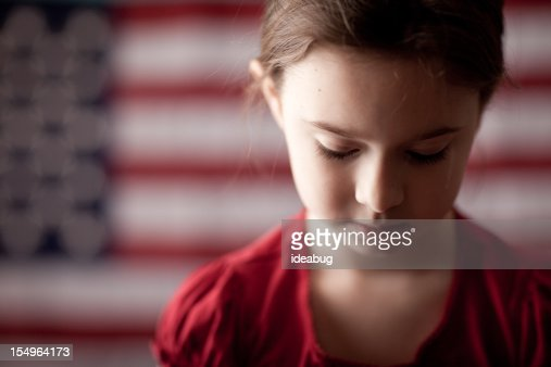 Sad Young Girl Looking Down in Front of American Flag