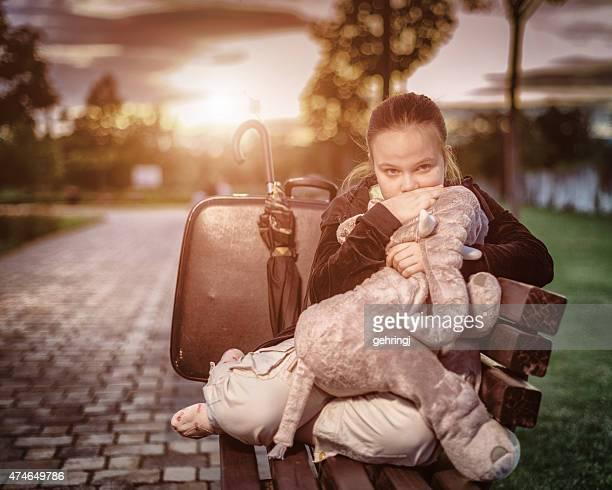 Triste giovane ragazza seduta su una panca