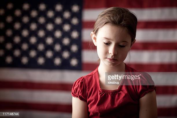 Sad Young Girl Thinking in Front of American Flag