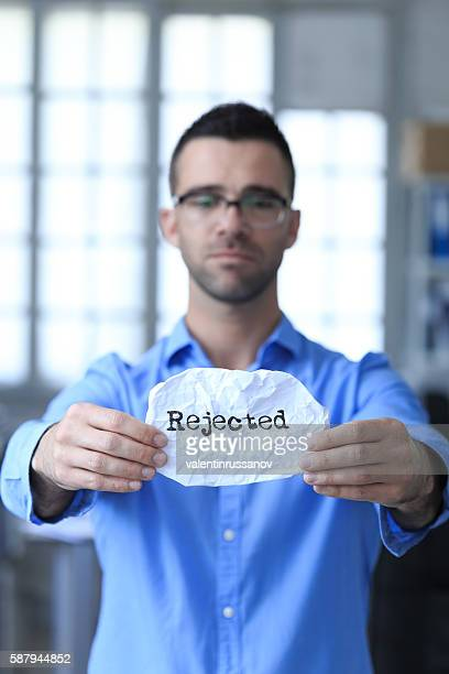 Sad young man holding a paper with sign 'rejected'